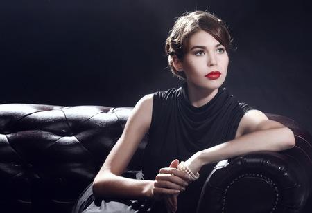 womanhood: Young beautiful woman in black dress sitting on the sofa
