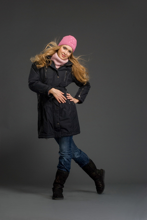 Young beautiful woman at studio in winter clothes