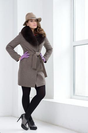 Young girl in studion posing at coat