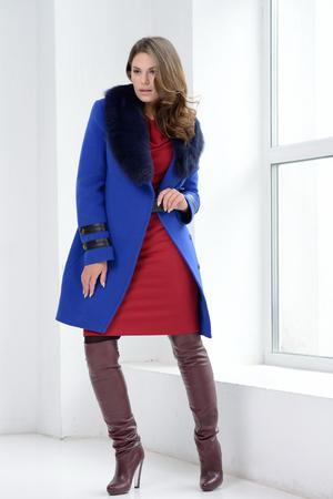 Young girl in studio posing at coat