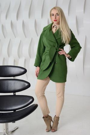 Young girl in studio posing in coat
