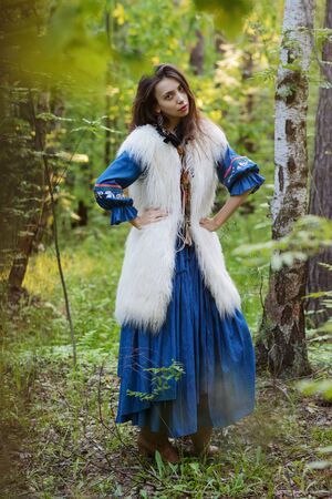 Young gipsy in blue dress at the forest Stock Photo