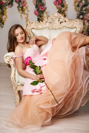 Young beautiful girl at the flower interior Stock Photo