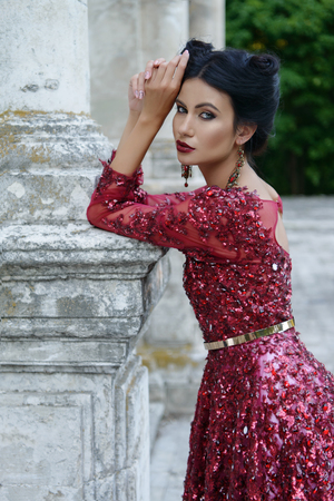 Schöne junge Hexe im purpurroten Seidenkleid