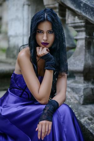 Mooie jonge heks in lila zijden jurk