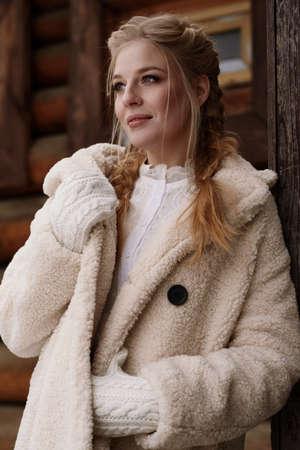 Beautiful Russian girl wearing costume in Russian style posing near wooden cottage