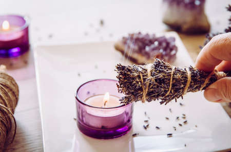 Person holding homemade herbal lavender (lavendula) smudge stick with smoke coming out, candles and amethyst crystal clusters for decoration. Spiritual home cleansing concept.