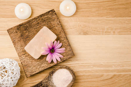 Bar of orange dry Himalayan crystal Salt Soap on wooden background with wooden spoon with pink orange Himalayan crystal Salt grains in. Flower blossom decoration. Alternative medicine concept. Standard-Bild