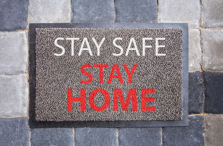 Disease avoid spread concept. Home doormat with text: Stay safe, stay home. Home decor with message.