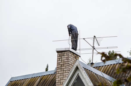 Chimney sweeper clears ash and soot from chimneys on cloudy autumn day.