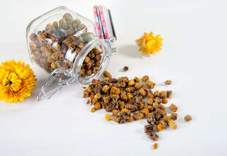 Alternative medicine, domestic honey bee made bee bread ( fermented flower and plant pollen ) inside small glass jar and scattered on white table. Flat lay view.
