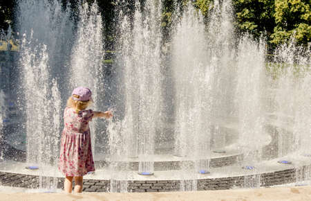 Children playing in water splashing fountain in public park, having fun on warm sunny summer day.