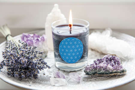 Burning glass candle with homemade sign showing Flower of Life symbol in home interior with semi precious stone geodes. Spiritual symbols in home decor concept.
