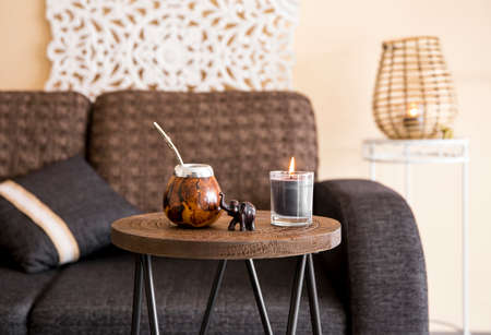 Close up view of yerba mate tea calabash with metal bombilla straw and elephant figurine on small table in modern living room, sofa couch background with oriental details.