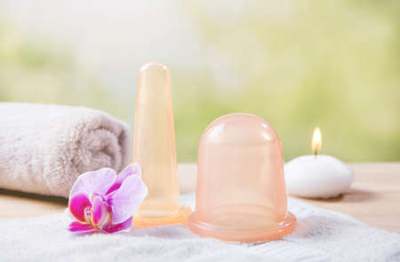 Remove body cellulite using big silicone massaging cupping tool, increases blood flow in skin tissue. Smooth skin with smaller face cupping tool. Still life studio composition.