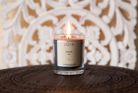 Tallinn,Harjumaa/Estonia-11MAR2020: Popular brand JOIK from Estonia, scented soywax candle burning on small wooden table with oriental wood carved background in cozy home.