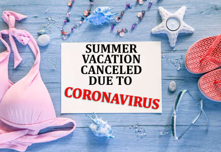 Abstract color background with text: Summer vacation canceled due to coronavirus. Pink bikini, coral flip flops and sunglasses, blue wooden background.