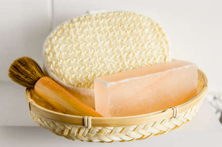 Bar of orange Himalayan crystal Salt Soap on wooden tray with cleaning bath sponge in bathroom.