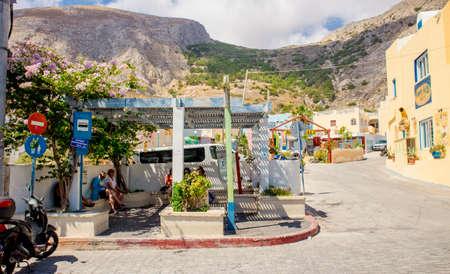Kamari, Santorini/Greece-14JUL2019: Kamari beach bus stop. Tourists sit and wait for the bus. Mesa vouno mountain in the background.