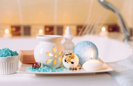 Home spa products on white ceramic tray: bar of soap, bath bomb, aroma bath salt, essential and massage oils, candle burning, aroma oil lamp inside bathroom by tub, water running. Wintertime self care
