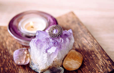 Acupressure massage ring on amethyst crystal cluster. Acupressure is an alternative medicine technique with physical pressure is applied to acupuncture points with the aim of clearing blockages.