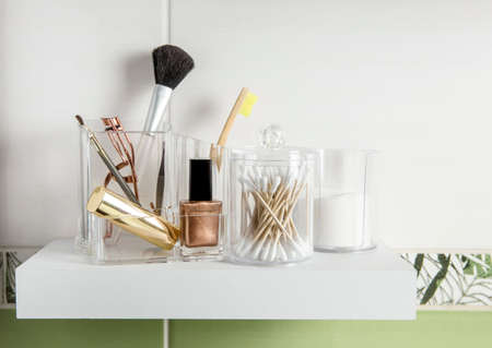 Makeup products organizing in bathroom concept. Beauty products in organizer container box on tidy way on minimalist shelf. Cotton pads stacked