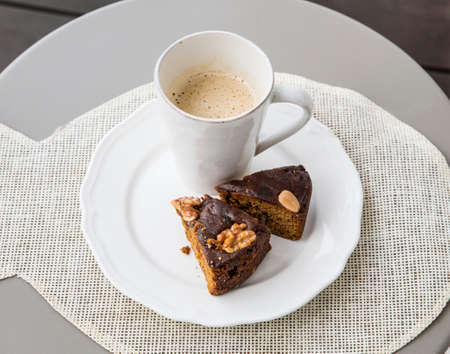 Two slices of Bolo de mel is a traditional cake from the Madeira Islands on white plate, white cup of coffee on the background.