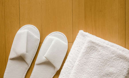 Flat lay view of pair of white new clean spa disposable spa slippers and white clean towels in stack.
