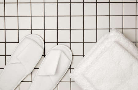 Flat lay view of pair of white new clean spa disposable spa slippers and white clean towels in stack. Copy space on white tile background. Beauty care lifestyle.