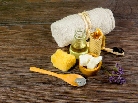 Using natural material products in home, different cosmetic products in bathroom. Minimizing ecological footprint concept. Bamboo bath towel, biodegradable bamboo toothbrush, clay mask, coconut oil. Banque d'images