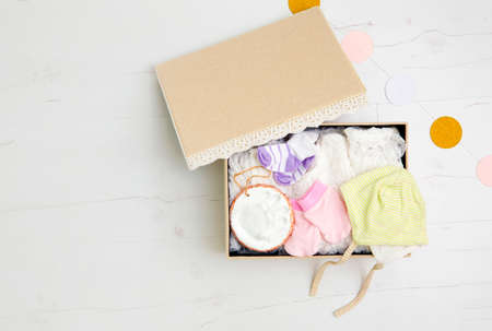Vintage keepsake box for preserving baby`s first clothes and things concept. Newborn baby clothes in box hat, gloves, dress, socks, clay hand print to preserve mother`s and baby`s first memories.