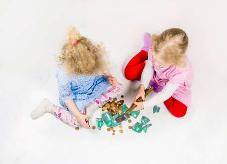 Top view of two young blond girls sisters sit on white floor braking a ceramic piggy bank. Broken piggy bank on floor, euro coins scattered around. Children collecting money and using savings concept.
