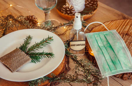 Christmas eve holiday party decorated table set with disposable medical mask and alcohol hand sanitizer bottle. Coronavirus (Covid 19) spreading prevention concept. Christmas micro led lights wire.