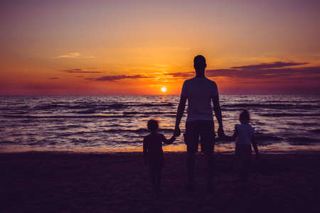 Father with two young daughters standing on tranquil beach at night with sun setting in to the sea. Family vacation time concept. 版權商用圖片