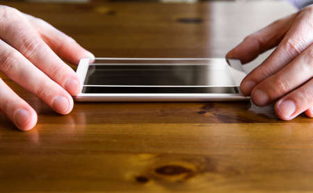 Man hands fingers hold smartphone screen protective covering glass on top of smartphone, about to install the protection glass. Protecting from scattering, scratches and cracks concept.