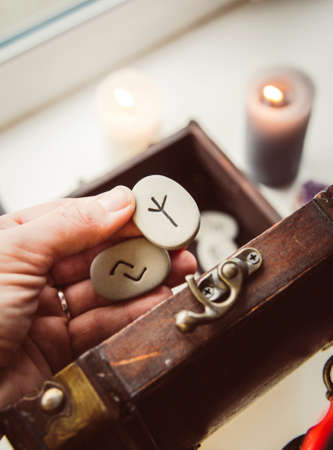 Hand holding rune stones, taking out of the wooden box container, self-prophecy concept. Candles burning. Stock Photo