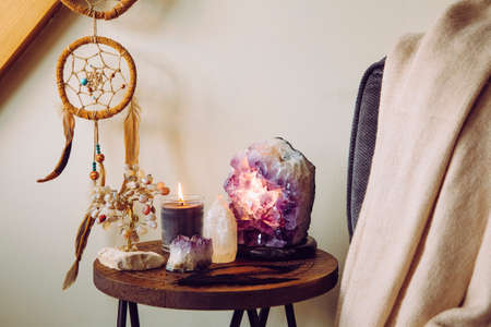Relaxing home shrine with relaxing objects, amethyst cluster geode lamp illuminated, scented candle burning, selenite tower stone, crystal wire tree and dream catcher.