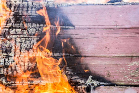 Detail view of burning painted wooden board wall fallen apart, lot of smoke, flames and charcoal. Home house fire concept.