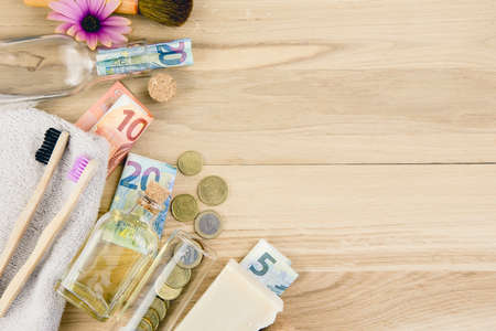 Set of different zero waste beauty products on wooden background with euro money bank notes around them, zero waste sustainable lifestyle true cost concept.