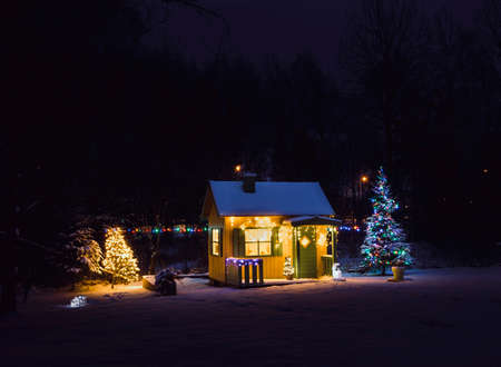 Wooden painted yellow private children`s play house in home garden, decorated with Christmas LED string lights outdoors in cold winder night. Decorated Christmas fir tree. Zdjęcie Seryjne