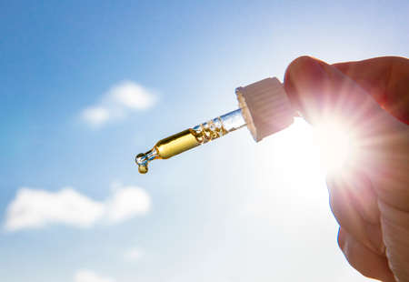 Hand holding dropper pipette with nice golden liquid D-vitamin against sun and blue sky on sunny day. Vitamin D keeps you healthy while lack of sun in winter, cure concept. Imagens