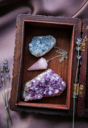 Witch tools inside beautiful old wood box. Rose quartz pendulum, natural amethyst and celestite crystal clusters. Dry lavender flowers on dark purple cloth. Alternative lifestyle concept.