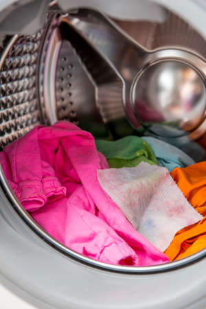 Color absorbing sheet inside a washing machine, allows to wash mixed color clothes without ruining colors concept. 스톡 콘텐츠