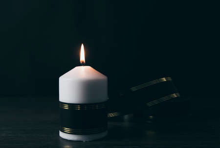 White candle with black ribbon, symbol of remembrance or mourning, black background. Lot of blank copy space for your text. Stock Photo