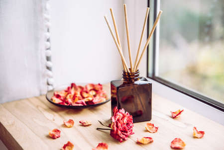 Brown glass bottle container with wood stick diffusers on home wooden window sill with beautiful dry pink rose petals for decoration. Minimalist air freshener concept.