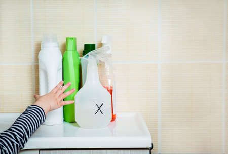 Child`s hand reaches out to household chemicals. Keep away from children. Safety Hazard for kids at home.