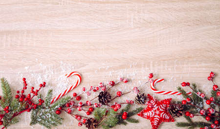 Flat lay view of Christmas frame background. Branches with red berries, felt star ornaments, red candy canes and spruce branches, copy space.