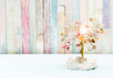 Feng shui gem tree, also called feng shui crystal tree is used for spiritual feng shui cures for love to feng shui for money. Isolated on colorful pastel wooden board background. Lens flare. Stockfoto