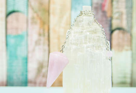 Using crystal Selenite tower for loading rose quartz pendulum, light blue table and pastel color wooden board background. Divination and fortune telling concept.