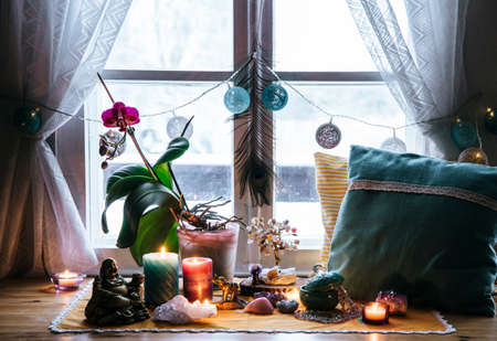 Feng Shui altar at home in living room or bed room. Attracting wealth and prosperity concept. Crystal clusters, wire tree with gemstones, golden Buddah figure on table and window sill. Vibrant colors. 免版税图像